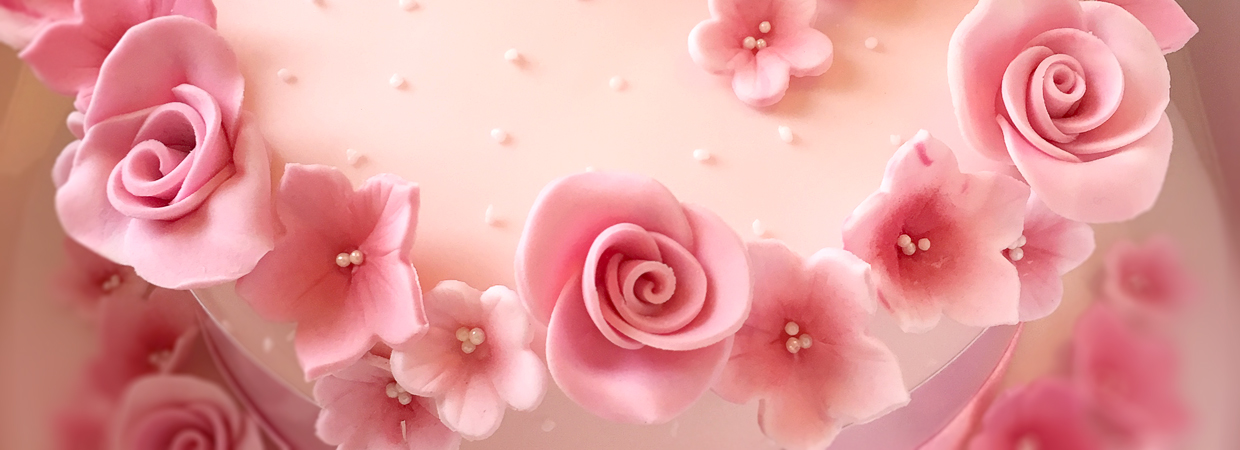 Close up of pink flower roses decorating cake